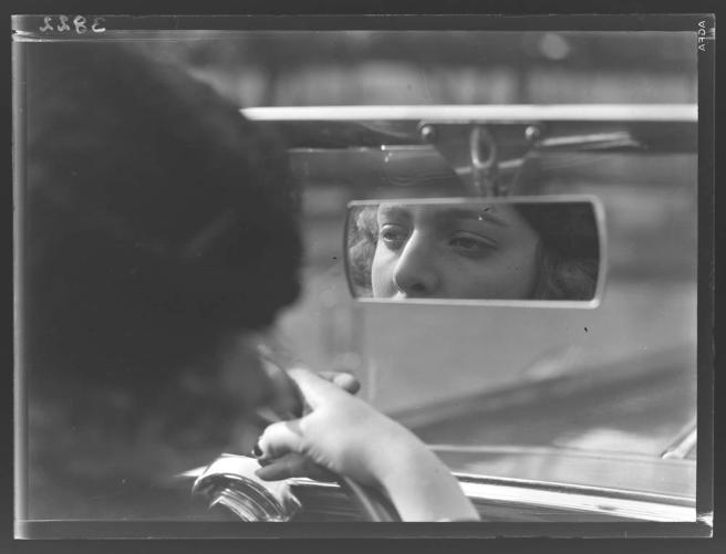 [Woman looking at reflection of herself in rearview mirror], 193